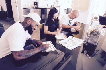 Rapper The Game, left, and Darice Smolenski, center, sign paperwork making The Game co-owner of The Reserve medical marijuana dispensary in Santa Ana.
